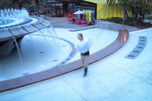 A cleaning person at the wading pool at Grand Park in downtown LA.